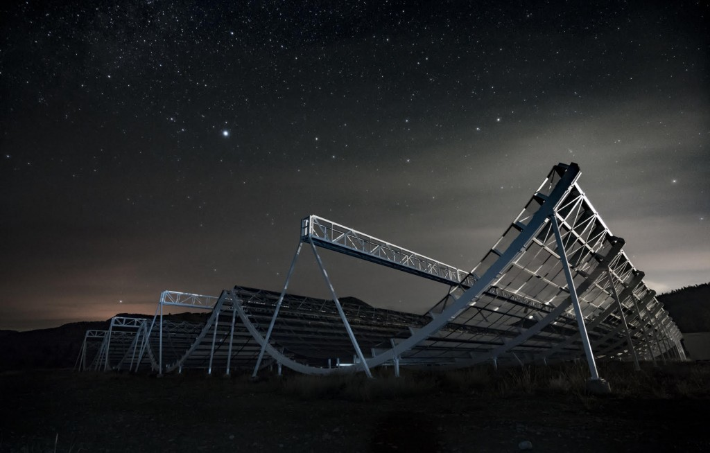 CHIME at night.  The telescope consists of four parabolic cylinders that are 20 m wide and 100 m long with a focal length of 5 m.  The telescope has no moving parts, instead relying on the earth's rotation to move the sky across its field of view.  The focal line of each cylinder is populated with 256 dual-polarization antennas that feed into a custom 2048-input radio correlator.